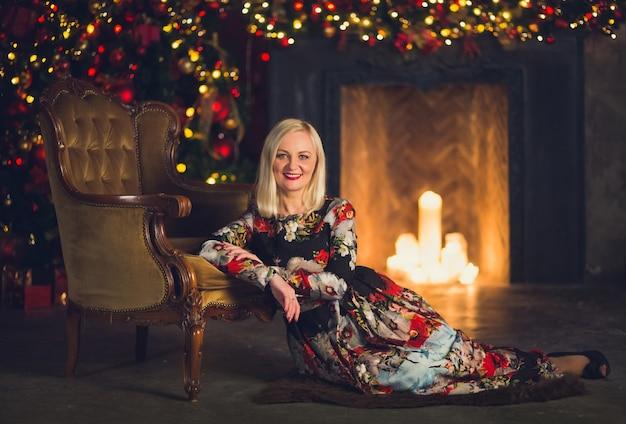 La donna si siede sul pavimento davanti al caminetto in abito floreale contro l'albero di natale si appoggia su una poltrona