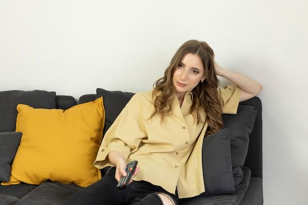 Una donna si siede a casa sul divano e guarda la tv.