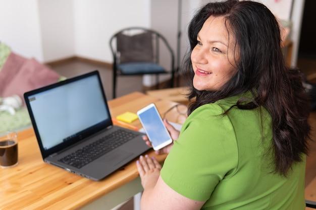 Una donna seduta a casa alla scrivania lavora con un laptop nei social network