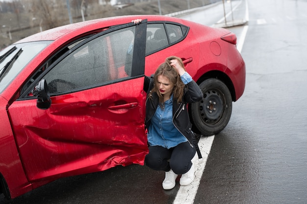 La donna si siede vicino a un'auto rotta dopo un incidente, chiedere aiuto all'assicurazione auto