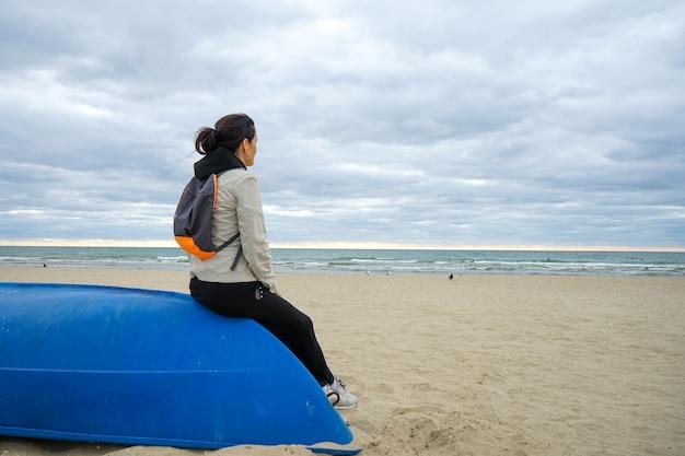Una donna siede su una barca capovolta situata su una spiaggia sabbiosa deserta e guarda il mare