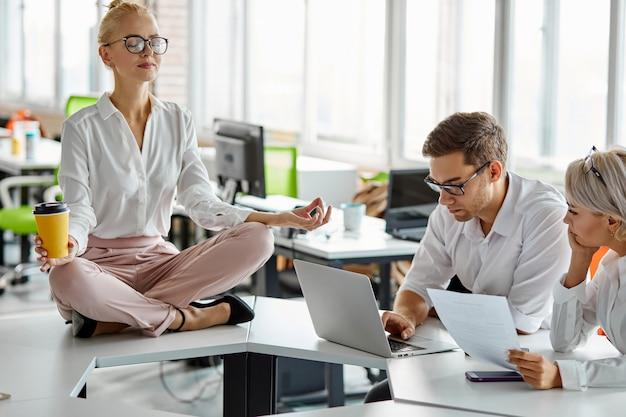 Donna si siede rilassante mentre altri hanno un brainstorming al lavoro