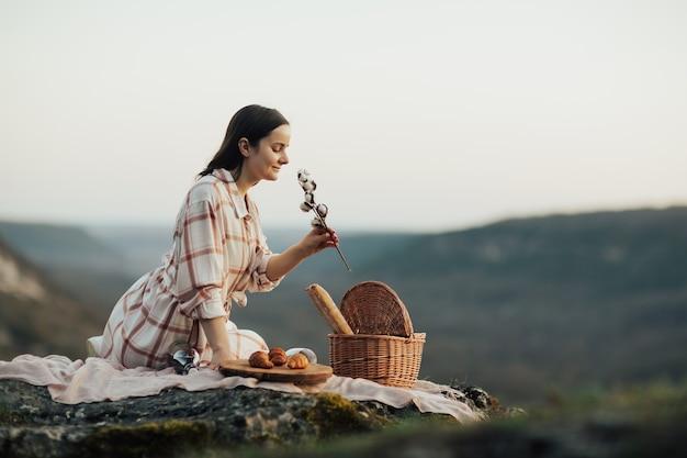 Donna si siede su una montagna rocciosa al picnic con croissant e vino