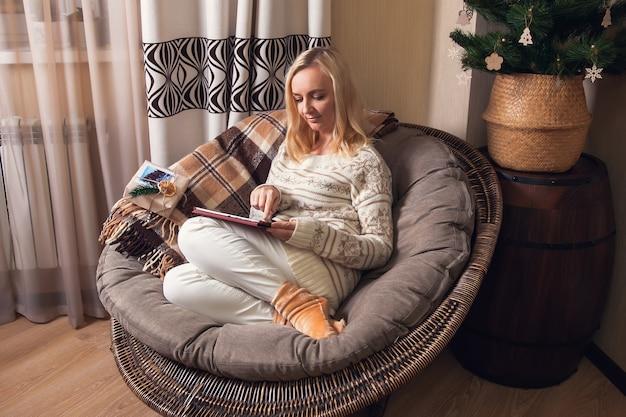 La donna si siede su una sedia rotonda e guarda e tocca il tablet con il dito