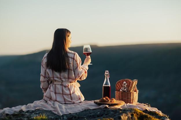 La donna si siede su una pietra sulla montagna e tiene un bicchiere di vino