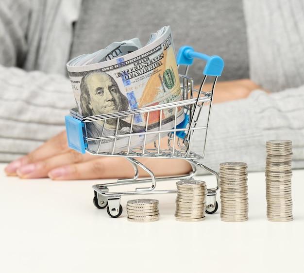 La donna si siede a un tavolo, pile di monete bianche e un carrello in miniatura con dollari usa. concetto di risparmio, vendita, tasse