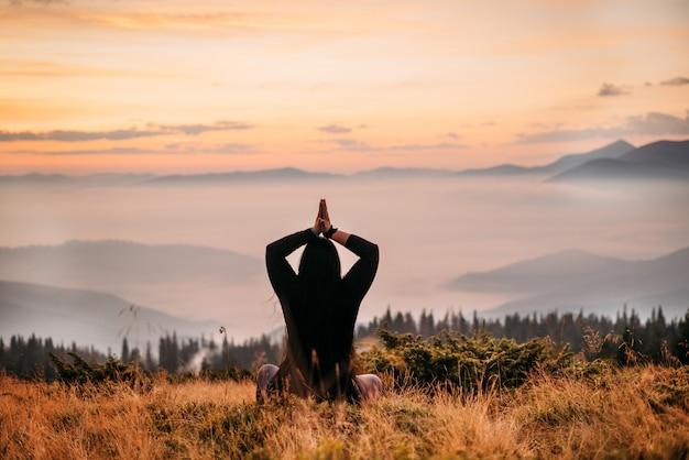 La donna si siede sulla cima di una montagna al sorgere del sole.