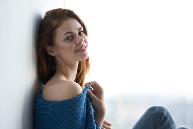La donna si siede sul davanzale della finestra ricoperta da una coperta dall'aspetto attraente