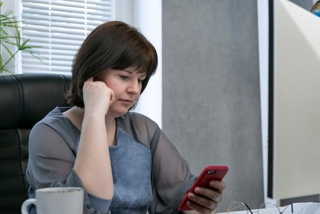 La donna si siede sul posto di lavoro e guarda lo smartphone. smm manager funzionante. promozione dei social network.
