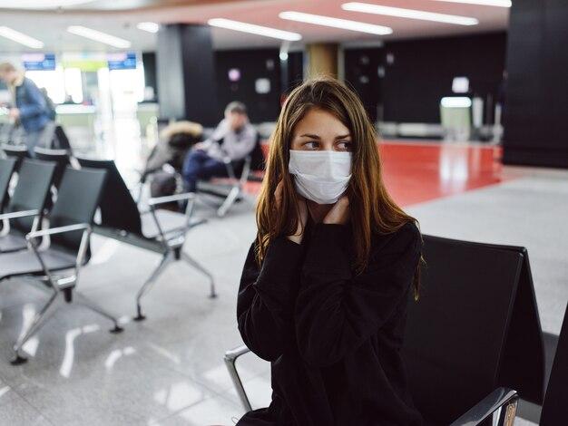 Donna seduta in aeroporto che indossa una maschera medica a lungo in attesa di un volo