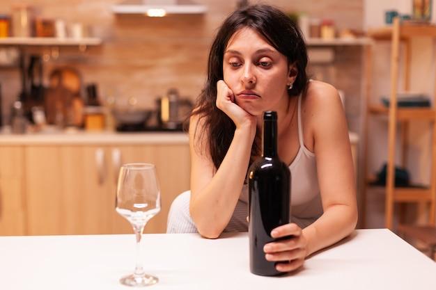 Donna seduta da sola con una bottiglia di vino rosso in cucina a causa dell'espressione. persona infelice che soffre di emicrania, depressione, malattia e ansia che si sente esausta.