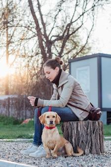 Donna che si siede nel cortile con il suo cane