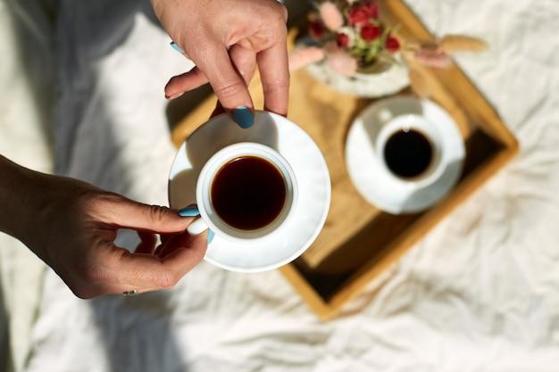 Donna seduta sul letto e beve caffè durante la luce del sole del mattino, colazione a letto.