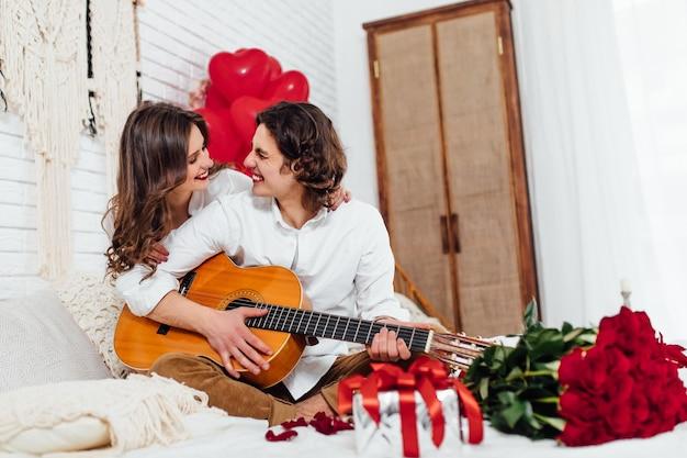 Donna seduta sul letto e uomo che suona la chitarra per lei, guardandosi l'un l'altro, concetto di san valentino