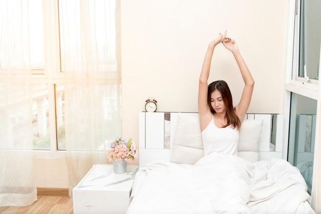 Donna che si siede su un letto con le sue mani in su