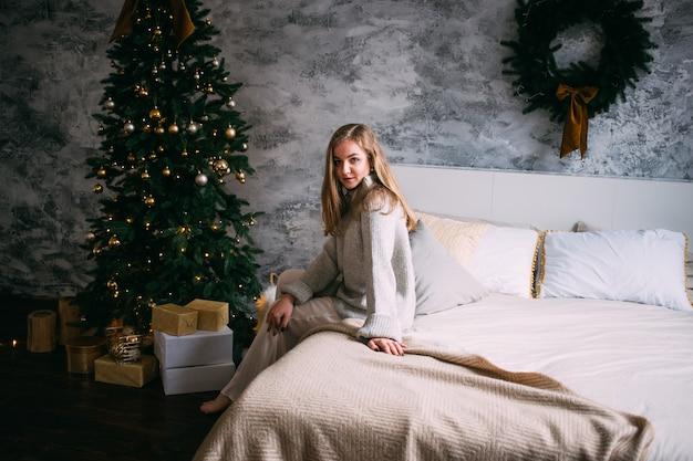 Donna seduta in camera da letto con decorazioni natalizie