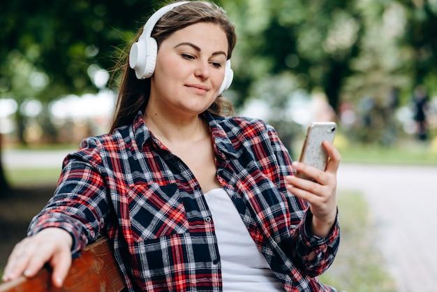 Donna seduta su una panchina in cuffia, guardando uno smartphone