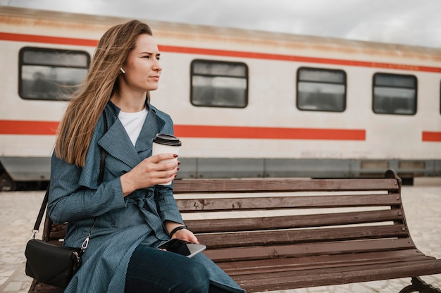 Donna seduta su una panchina e tenendo il caffè