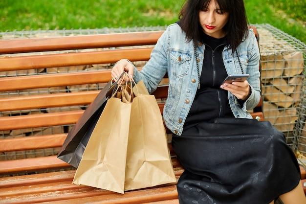 Donna seduta su una panchina nel parco borse della spesa, tenendo in mano lo smartphone, digitando un messaggio di testo