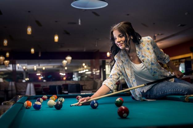 Donna seduta sul tavolo da biliardo andando a fare un successo