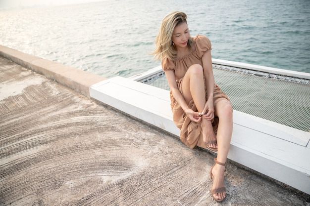 Donna seduta in riva al mare che indossa le scarpe, mettendo le scarpe.