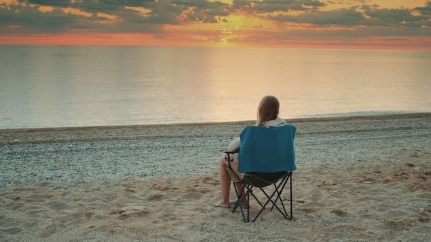 Donna seduta sulla sedia da campeggio e bere caffè. rilassarsi e godersi la natura. ammirando l'alba sul mare.