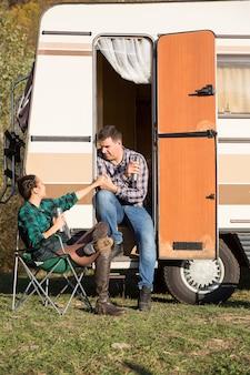 Donna seduta su una sedia da campeggio e guardando il suo ragazzo seduto sulle scale del loro camper retrò.