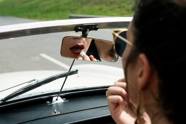 Donna che si siede in una macchina che mette rossetto sulle labbra con specchietto retrovisore