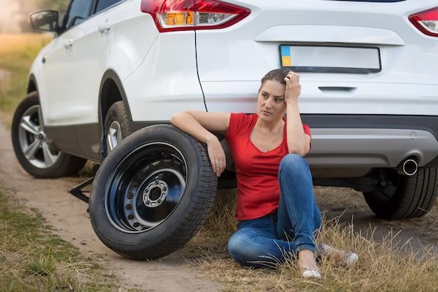 Donna seduta accanto all'auto con la gomma a terra e in attesa di aiuto