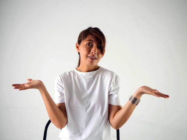 Donna seduta su una sedia, alza le mani con le espressioni facciali, agisce come se non le importasse tutto. emozione del modello in posa