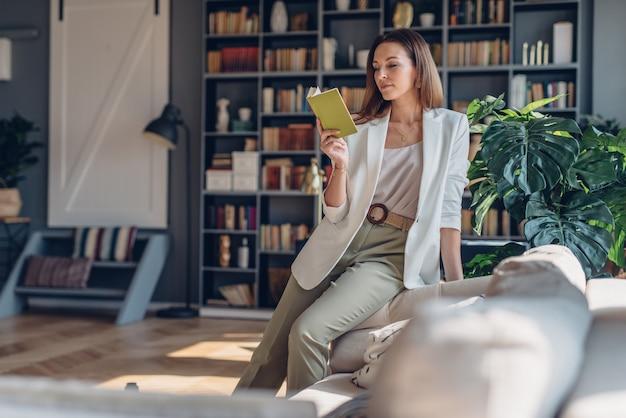 Donna seduta sul divano al mattino, leggendo un libro a casa.