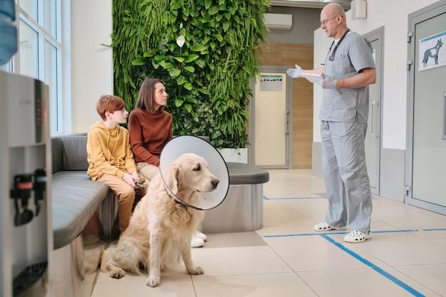 Donna seduta sul divano con il suo animale domestico e parlando con il medico veterinario nel corridoio della clinica
