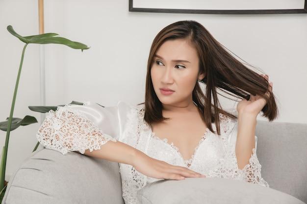 Una donna seduta stordita e distratta sul divano grigio di casa ragazza tirandole i capelli con la mano