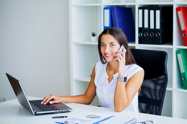Donna seduta alla scrivania, lavorando sul computer portatile in un ufficio moderno.