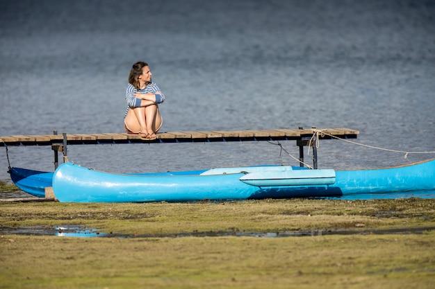 Donna seduta sul molo del lago moquehue in patagonia argentina