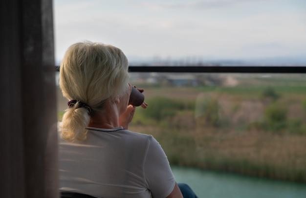 Donna seduta gustando un drink tranquillo su un balcone all'aperto