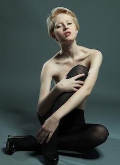 Donna seduta in posa alla moda che indossa collant neri black
