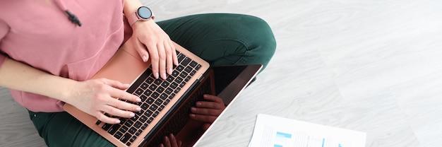 Donna seduta sul pavimento con laptop e documenti vista dall'alto lavoro a distanza durante la pandemia di covid