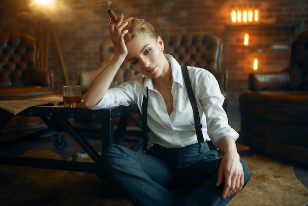 Donna seduta sul pavimento con whisky e sigari