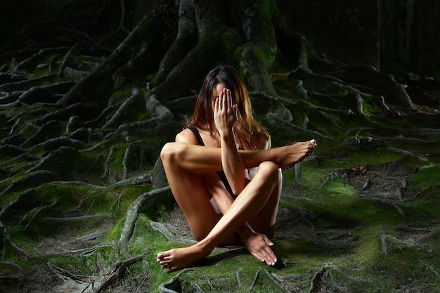 Donna seduta a terra nella foresta praticando yoga sotto un albero gigantesco