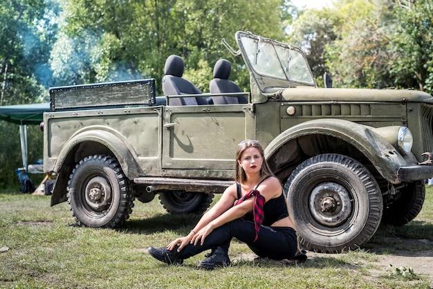 Donna seduta per terra vicino a un'auto militare