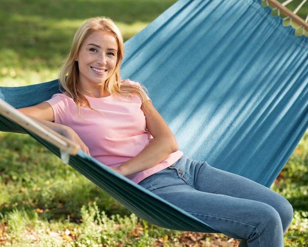 Donna seduta in amaca nel parco