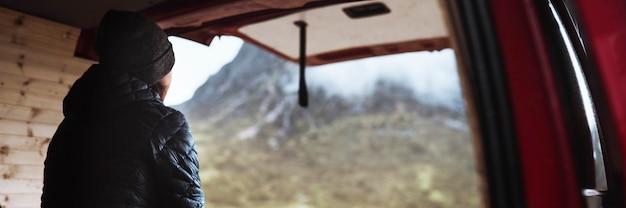 Donna seduta nel suo camper guardando le montagne
