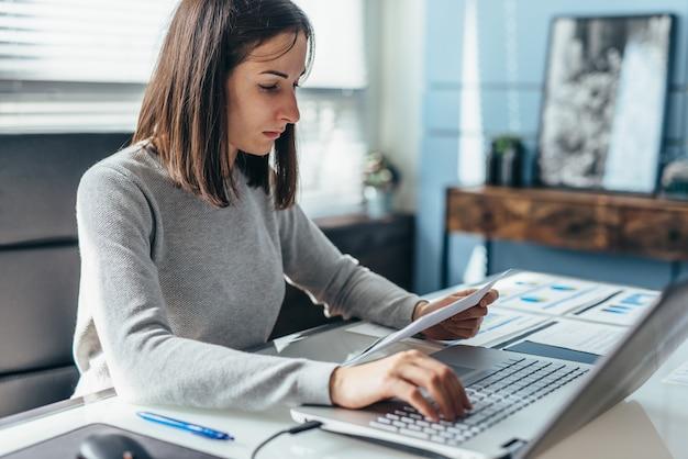 Donna seduta alla sua scrivania in ufficio e al lavoro.
