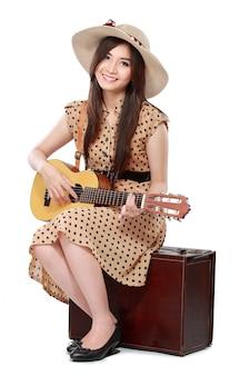 Donna che si siede sulla sua valigia mentre suona la chitarra
