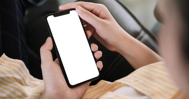 Donna che si siede e che tiene derisione dello schermo in bianco sul telefono cellulare