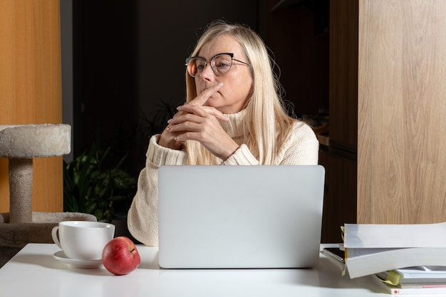 Donna seduta al computer portatile in ufficio a casa e guardando pensieroso in lontananza, donna premurosa prendersi una pausa dal lavoro