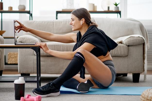 Donna seduta al computer portatile, formazione in linea in linea. persona di sesso femminile in abbigliamento sportivo, allenamento sportivo internet, interno della stanza