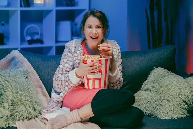 Donna seduta nel divano del salotto a guardare il programma interessante divertente e indicando la condivisione con il mangiare popcorn di notte