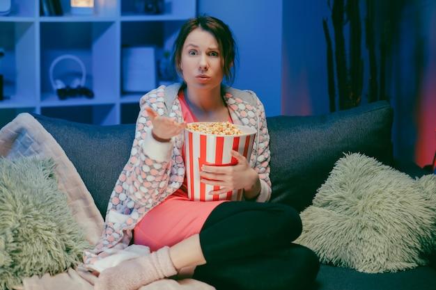 Donna seduta nel divano del salotto a guardare il programma interessante e indicando la condivisione con il mangiare popcorn di notte.